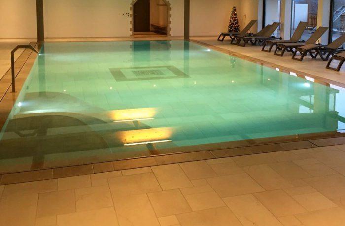 Spa et piscine à débordement avec système de traitement d'eau automatique.